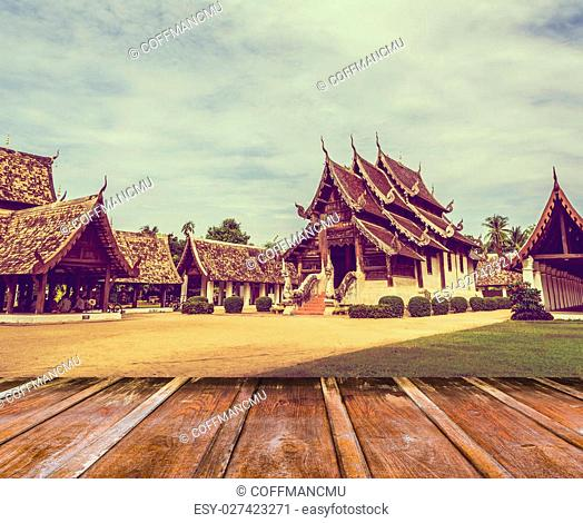 vintage tone image of Wat Ton Kain, Old temple made from wood in Chiang Mai Thailand and wood table in foreground