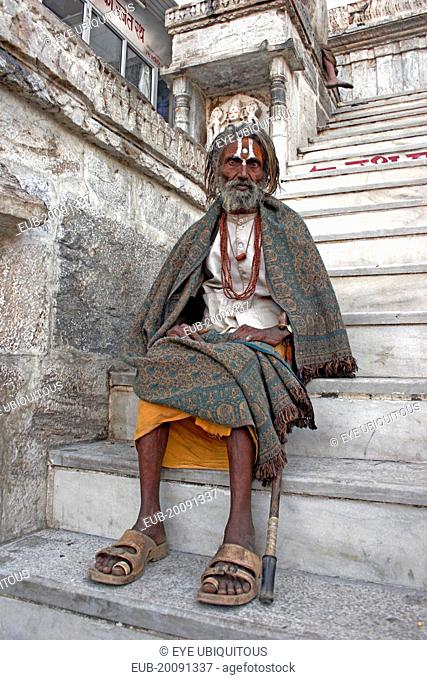 Elderly male Hindu beggar sitting on steps outside the Jagdish Temple wrapped in blanket shawl with painted forehead and grey beard