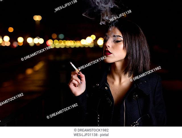 Portrait of smoking young woman at night