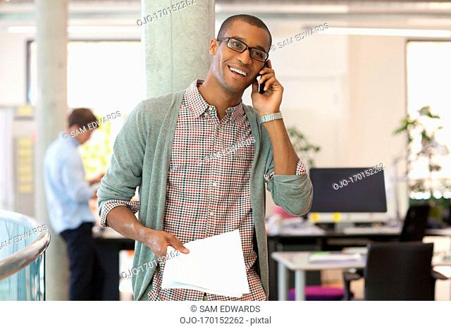 Businessman with paperwork talking on cell phone in office