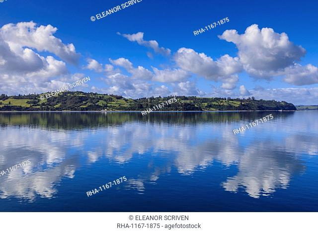 Castro inlet reflections, rural scene, fluffy clouds and rolling hills, Isla Grande de Chiloe, Chilean Lake District, Chile, South America