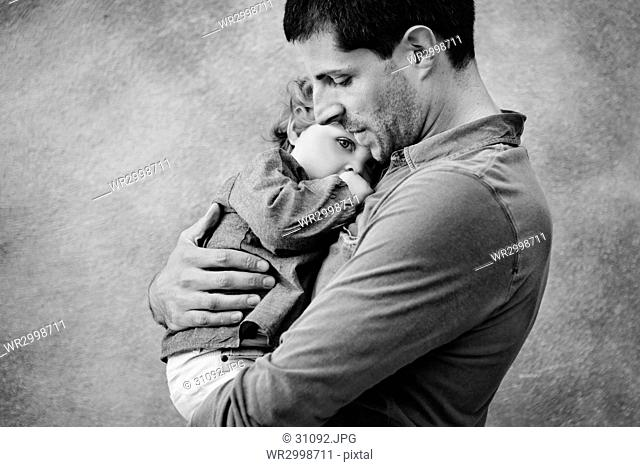 Side view of man hugging young girl