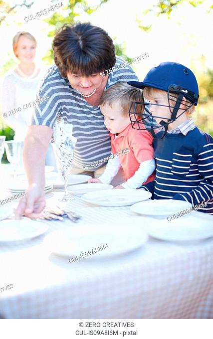 Boys and grandmother setting dinner table outdoors