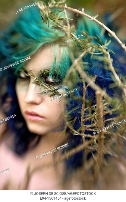 Portrait of a 19 year old woman with multi-colored hair with exotic make up engulfed in the roots and branches of a rosemary plant in a forest