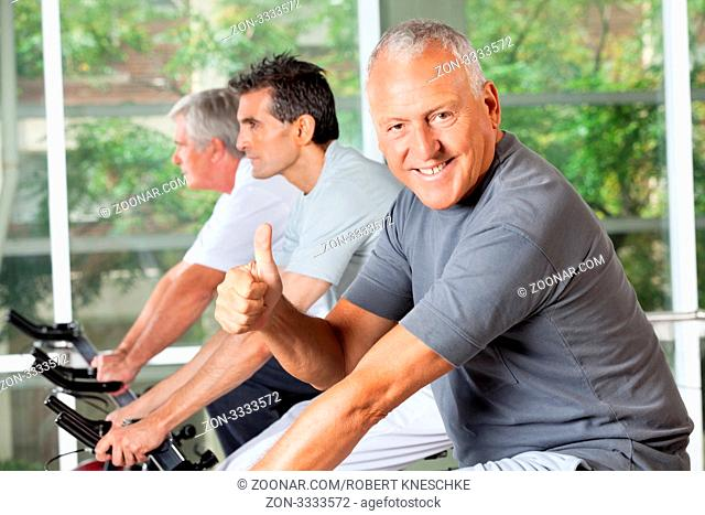 Lachender Senior im Fitnesscenter beim Spinning-Kurs hält seinen Daumen hoch