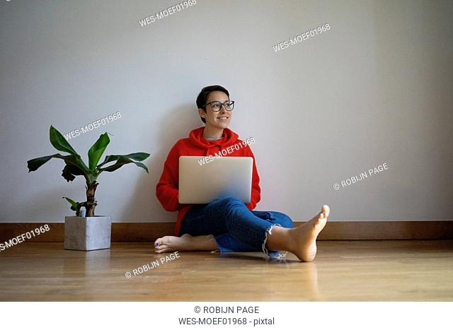 Young woman sitting on floor, using laptop