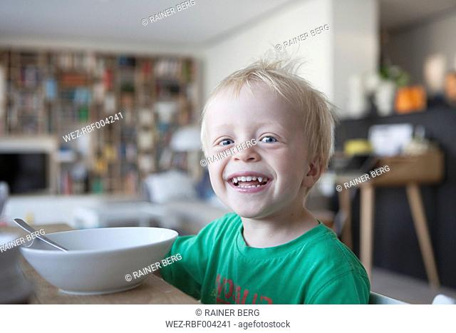 Portrait of happy little blond boy at home