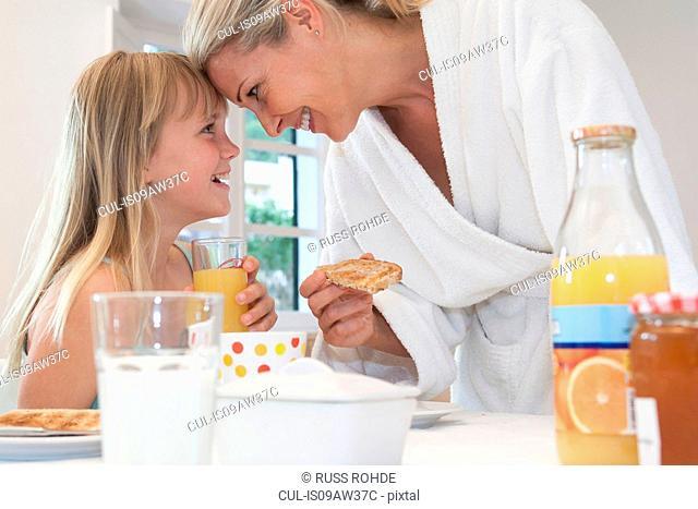 Mother and daughter having breakfast indoors