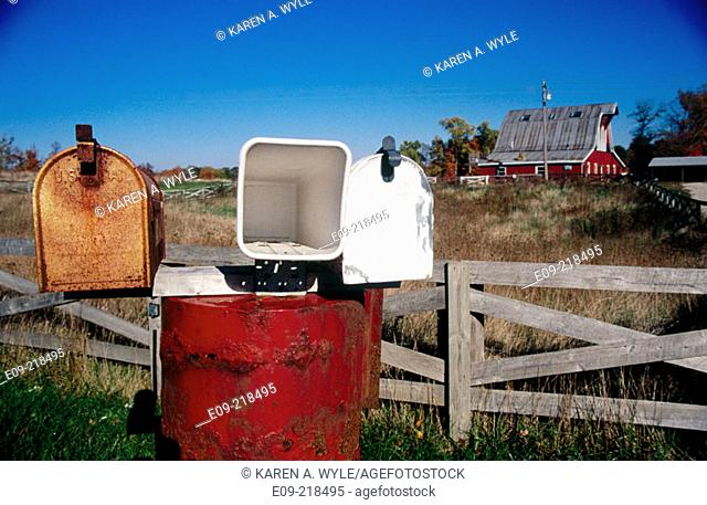 Rusty old mailbox, new white metal mailbox, and newspaper tube all mounted on wooden fence, rural Indiana, U.S.A