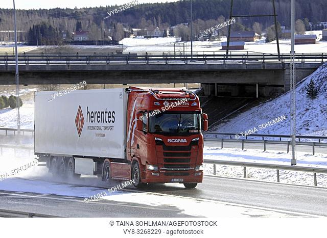 Salo, Finland - March 9, 2019: Red Scania S500 truck of Herentes pulls FRC trailer along wet motorway on a sunny day of early spring in Finland