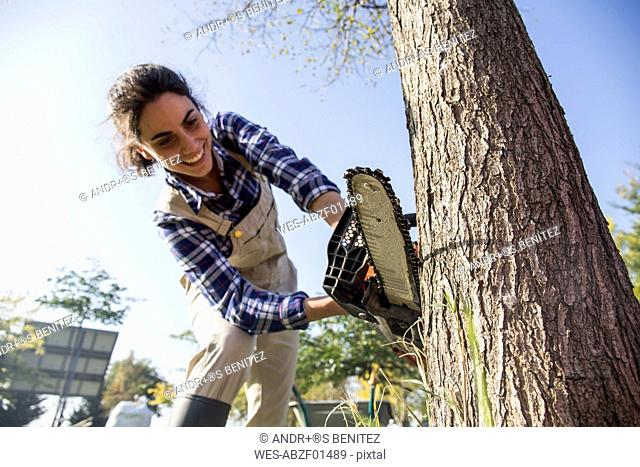 Woman on farm cuttiing tree with chain saw