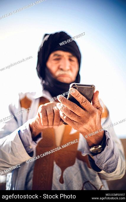 Senior man using cell phone in Smara refugee camp, Tindouf, Algeria