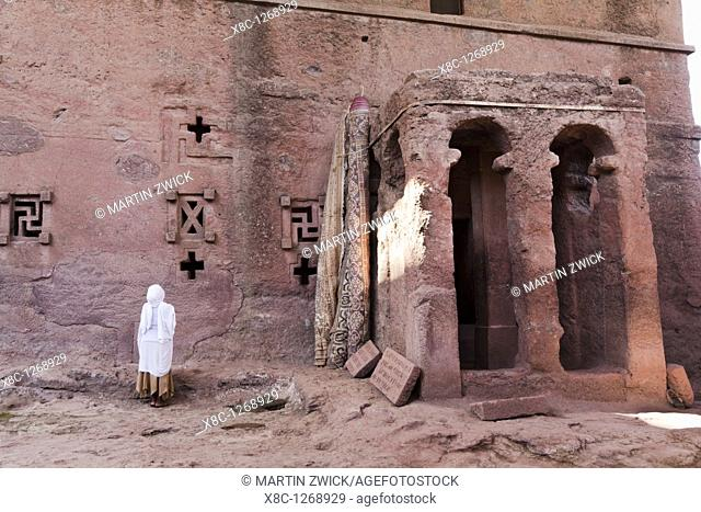 The rock-hewn churches of Lalibela in Ethiopia  Pilgrim praying in front of a church  The churches of Lalibela have been constructed in the 12th or 13th century...