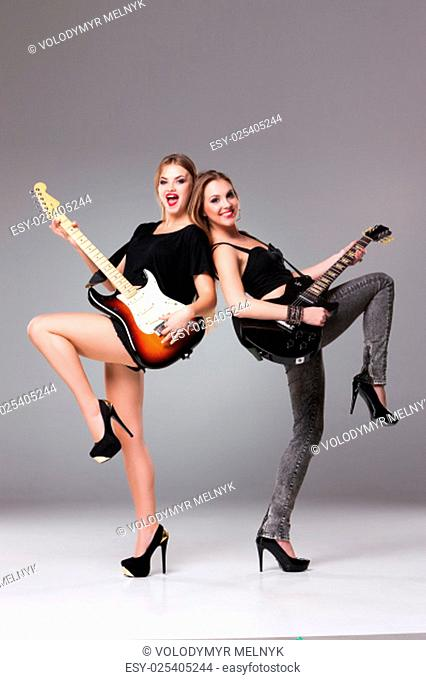 Two beautiful girls with long hair playing guitars in rock style on a gray background