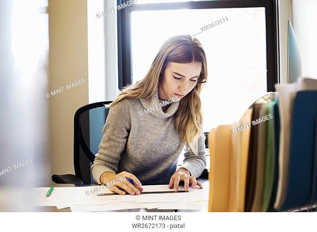 A young woman sitting at a desk in an office typing