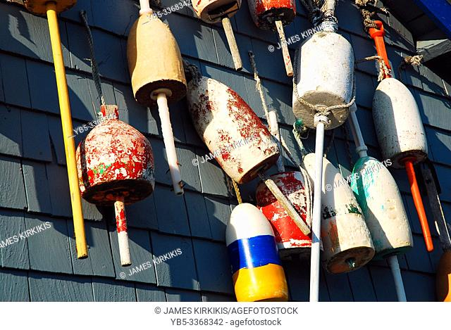 Colorful lobster buoys hang on a wall of a seafood restaurant