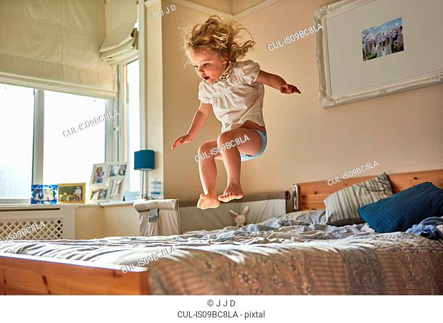 Female toddler jumping mid air on bed