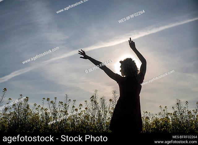 Silhouette woman with arms raised standing amidst oilseed rapes at sunset