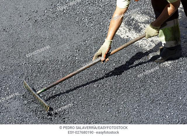 Worker at asphalting works a street