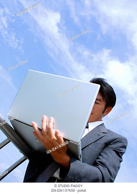 Low angle view of a businessman using a laptop