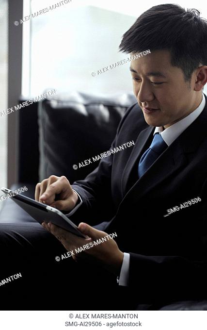 Young man wearing a suit, working on a tablet