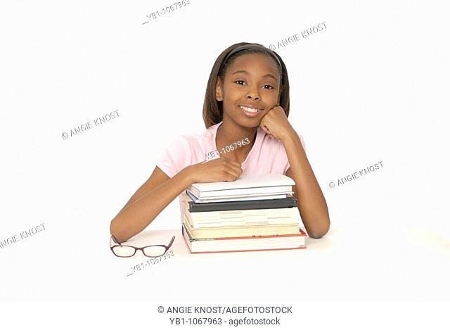 Smiling young student with stack of books and glasses