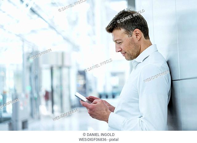 Businessman leaning against a wall using cell phone