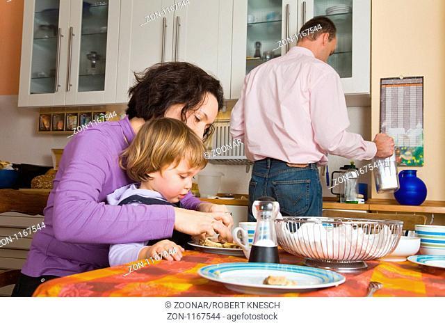 Familie mit einer Tochter zusammen in der Küche beim Essen