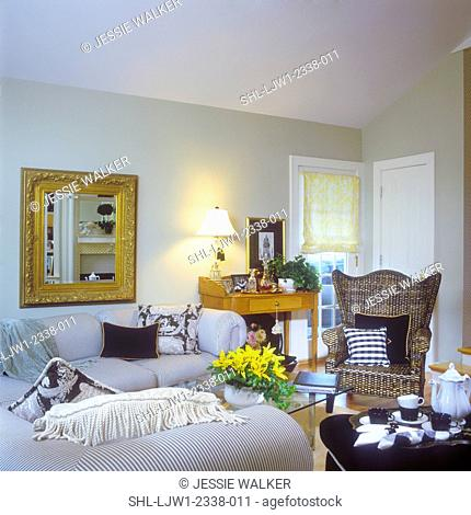 FAMILY ROOM - Sofa with black/white ticking. Wicker chair, coffee service in foreground , gold mirror, sage walls, maple desk with decanters, table lamp