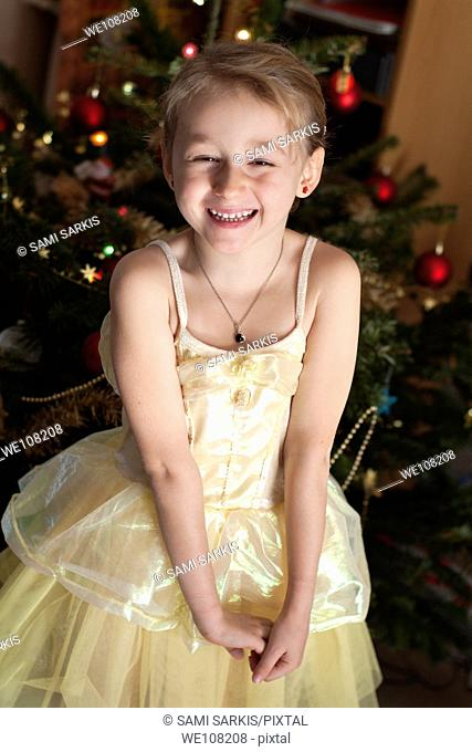 Little girl in a princess costume next to a Christmas tree