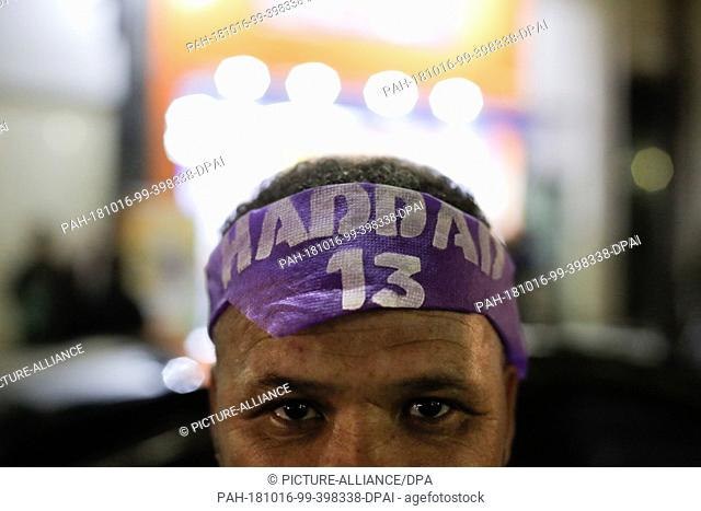 """15 October 2018, Brazil, Sao Paulo: 15 October 2018, Brazil, Sao Paulo: A man is wearing a scarf with the inscription """"""""Haddad"""""""" (candidate of the Left Workers'..."""