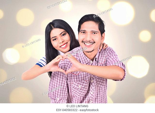 Romantic asian couple in love make a heart shape with their hands against blur light background