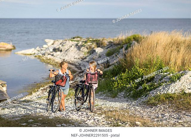 Young women cycling on sea coast
