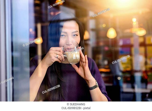 Mid adult woman drinking coffee in cafe window seat, portrait