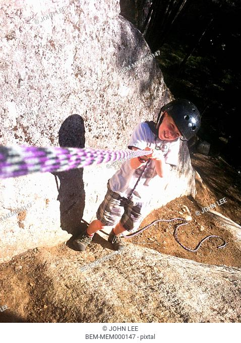 Caucasian boy climbing up wall on rope