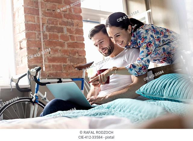 Couple drinking coffee using laptop on bed