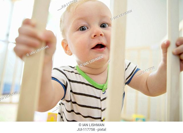 Portrait Of Smiling Baby Boy In Wooden Playpen At Home
