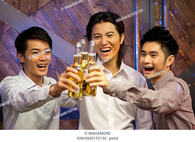 Friends holding beer and smiling happily