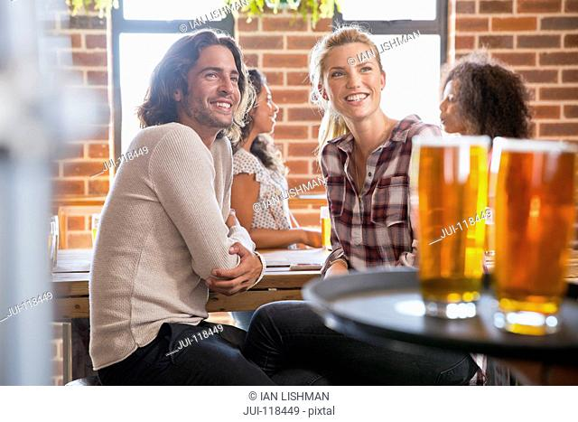 Waiter Serving Young Couple Meeting For Drink In Bar