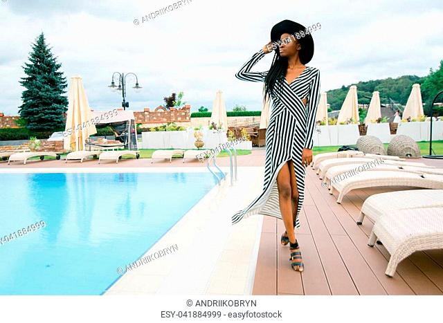 Attractive, pretty, tender, beautiful american woman in long dress in stripes and black hat. Model walking near pool of luxury hotel in Asia