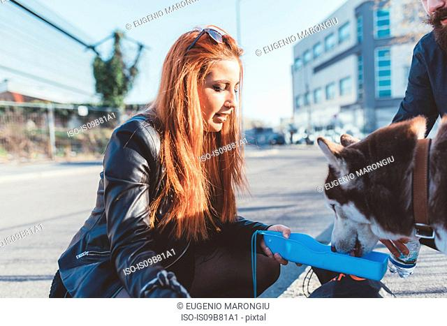 Red haired woman giving dog drink of water