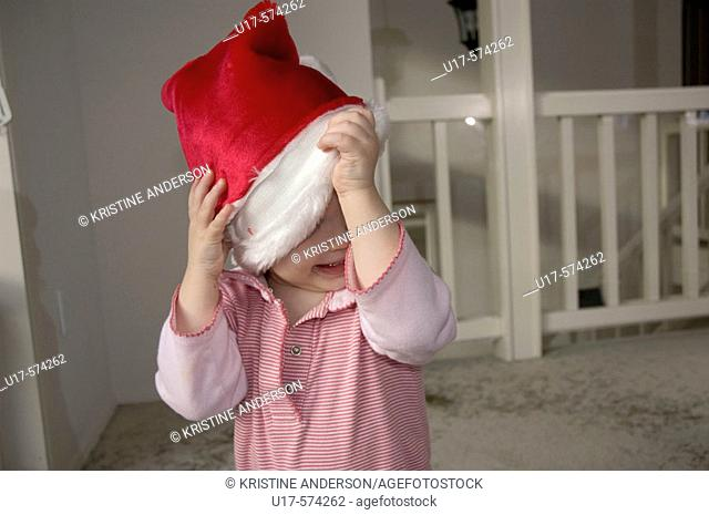 Toddler girl taking off Santa hat
