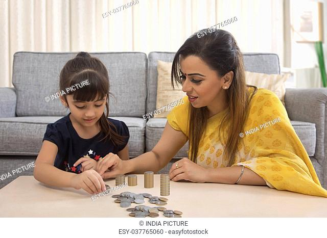 Mother and daughter stacking coins at home