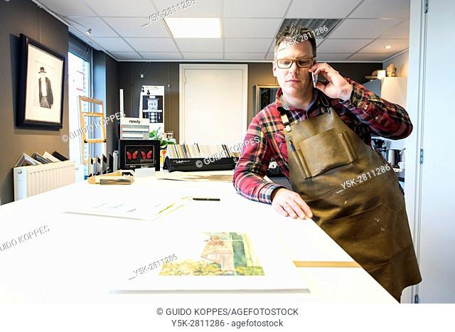 Goirle, Netherlands. Mid adult male craftsman and picture framemaker, talking into his smartphone during a mobile phonecall inside his workshop front office