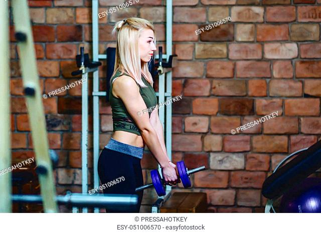 girl with dumbbell in gym workout in front of mirror