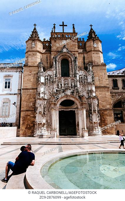 Tourists relaxing by a fountain in beautiful Praca 8 de Maio, May 8th square, with nice Santa Cruz church at back, Coimbra, Portugal