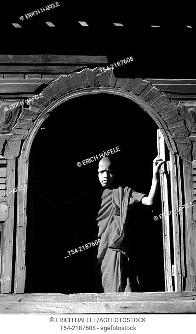 Young Buddhist monk at the window of a wooden monastery in Bagan