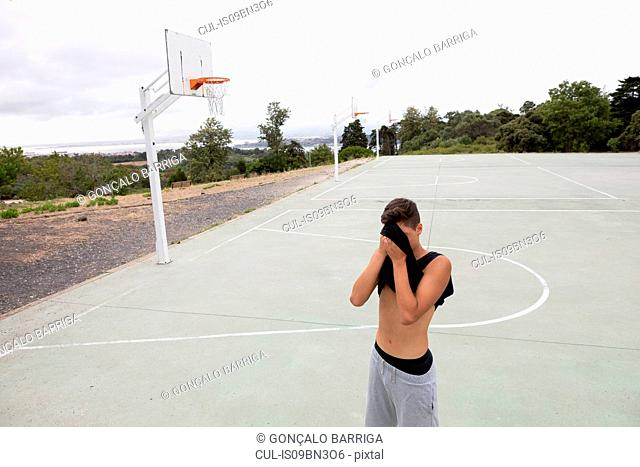Male teenage basketball player wiping his brow with vest on basketball court