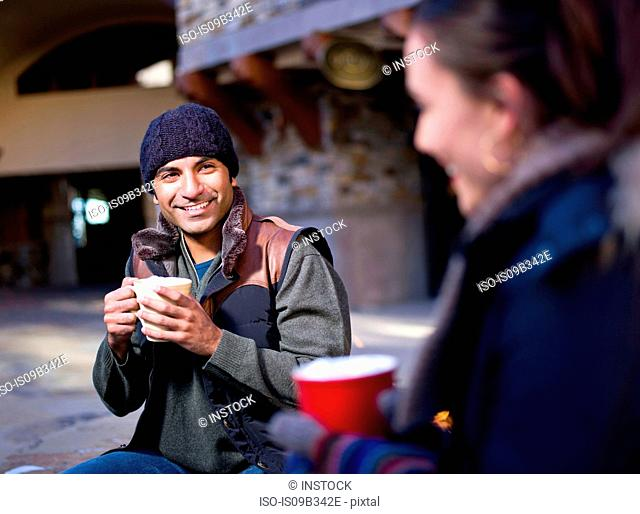 Young couple sitting outside holding hot drinks