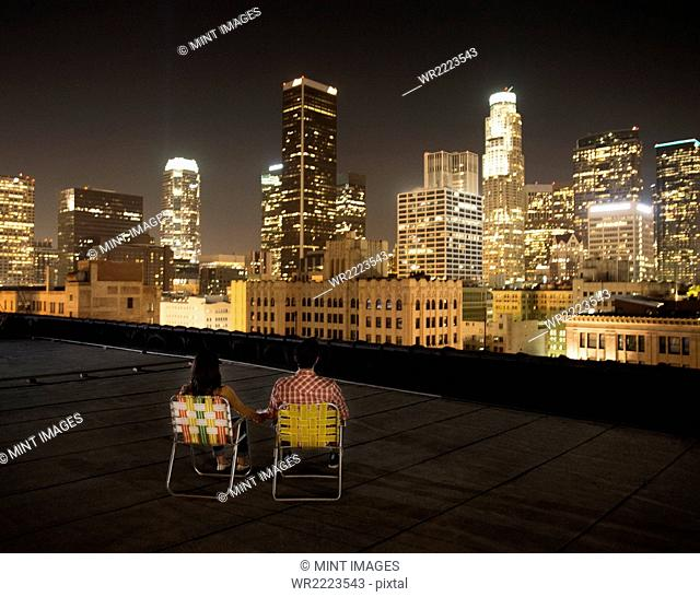 A couple on a rooftop overlooking Los Angeles at night, sitting side by side looking over the city